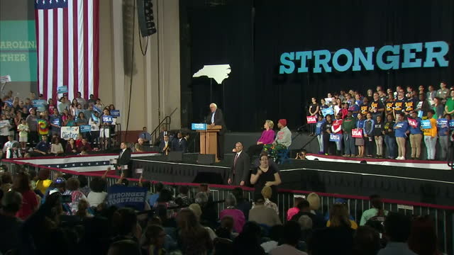 Interior shots of Bernie Sanders addressing cheering crowds at a Hillary Clinton rally in Pennsylvania with Hillary Clinton sat on stage listening on...