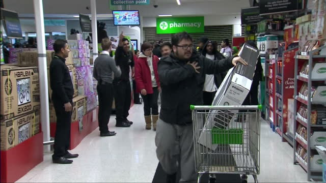 Interior shots of Black Friday shoppers in an ASDA store some people with trolleys carrying widescreen televisions other people running to find...