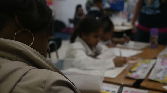 interior shots of black school children in an elementary school english lesson writing and doing exercises on january 22 2016 in flint michigan - feuerzeug stock-videos und b-roll-filmmaterial