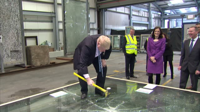 Interior shots of Boris Johnson MP London Mayor stepping onto shatter proof glass panel attempt to smash it with a hammer with Theresa Villiers MP...