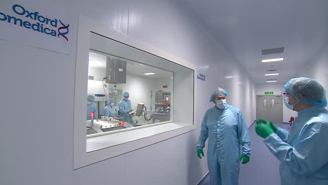 vídeos y material grabado en eventos de stock de interior shots of boris johnson watching scientists working during a tour at the manufacturing facility for the oxford/astrazeneca vaccine on the... - oxford oxfordshire