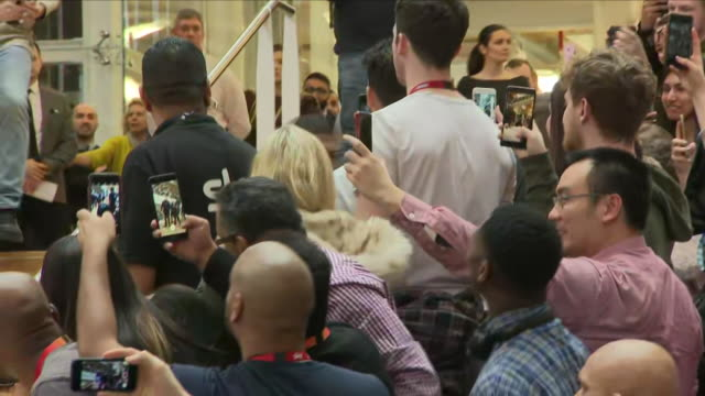 Interior shots of Boxer Anthony Joshua walking down steps through crowd and into Boxing press conference on 27th March London England