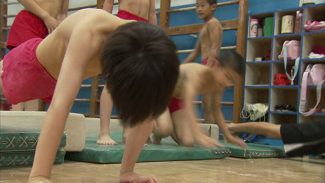 Interior shots of boys doing push ups in a gymnasium at Shichahai Sports School >> on August 2nd 2012 in Beijing China