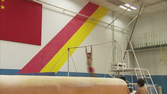 vídeos de stock, filmes e b-roll de interior shots of boys practising gymnastics skills on the pommel horse and high bar in a gymnasium at shichahai sports school>> on august 2nd 2012... - acrobata