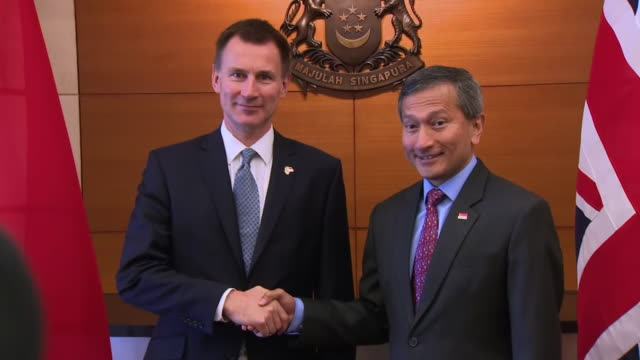 interior shots of british foreign secretary jeremy hunt mp meeting singapore minister for foreign affairs vivian balakrishnan who pose for handshake... - バッシャール・アル=アサド点の映像素材/bロール