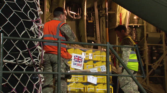 interior shots of british military personnel moving pallets, labelled with ukaid stickers, preparing humanitarian aid supplies to be flown to... - british military stock-videos und b-roll-filmmaterial