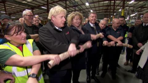 stockvideo's en b-roll-footage met interior shots of british prime minister boris johnson pulling christmas cracker with factory staff members before telling his own brexit joke on... - boris johnson