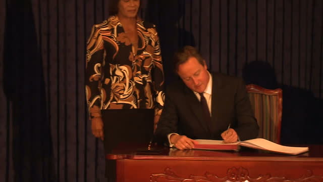 vídeos y material grabado en eventos de stock de interior shots of british prime minister david cameron signing the guest book before a bilateral meeting with jamaican prime minister portia simpson... - jamaiquino