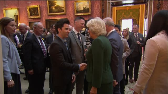 interior shots of camilla, duchess of cornwall and prince charles talking to guests and walking through hallway to meet more guests incl band members... - ヨーク公爵夫人点の映像素材/bロール