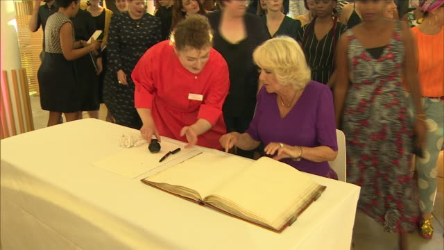 interior shots of camilla, duchess of cornwall, signing a visitors book and meeting authors at a '40 under 40' literary event at the british library... - signierstunde stock-videos und b-roll-filmmaterial