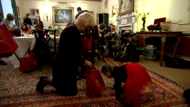 Interior shots of Camilla Duchess of Cornwall sitting on carpet with little girl looking into a bag of presents during dinner with children at...