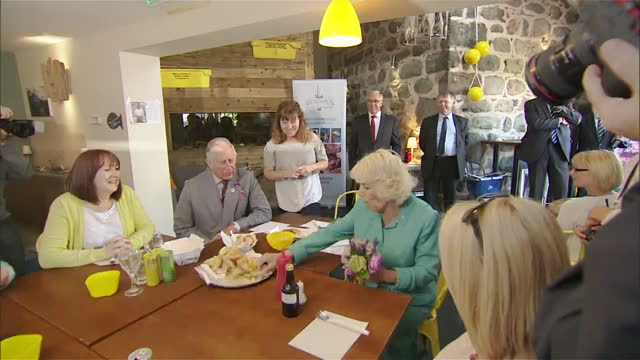 Interior shots of Camilla Duchess of Cornwall taking a seat and eating chips missing her mouth on July 5 2016 in Aberdaron Gwynedd Wales