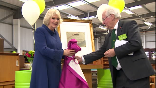 Interior shots of Camilla Duchess of Cornwall unveiling a plaque to commemorate the official opening of The Orchard and Emmaus Superstore and making...