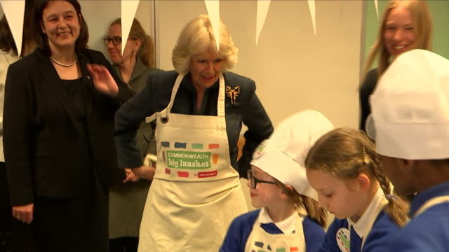interior shots of camilla the duchess of cornwall walking into a cooking class and putting on an apron including shots of camilla talking to children... - apron stock videos & royalty-free footage
