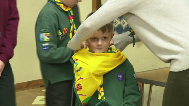 interior shots of catherine duchess of cambridge helping a cub put a sling around another cub during a first aid practise session at a cub scout pack... - cub scout stock videos and b-roll footage