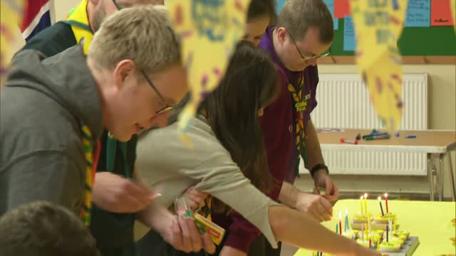 interior shots of catherine, duchess of cambridge helping cub leaders light candles on cup cakes to celebrate 100 years of cubs at a cub scout pack... - 6 7 years stock videos & royalty-free footage