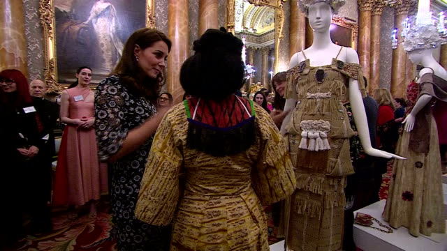 interior shots of catherine duchess of cambridge looking at a dress with fashion designer at a reception to mark the creation of the commonwealth... - designberuf stock-videos und b-roll-filmmaterial