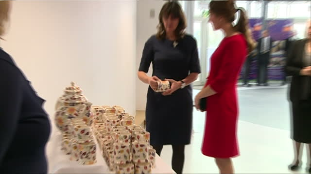 Interior shots of Catherine Duchess of Cambridge looking at a range of ceramic teapots and mugs being sold in aid of the East Anglia Children's...