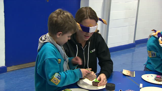 Interior shots of Catherine Duchess of Cambridge sat with a Beaver Scouts group and icing a cupcake whilst wearing a blindfold with the aid of a...