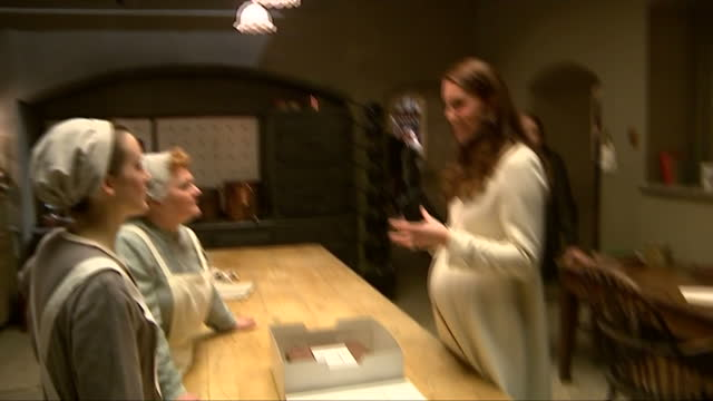 Interior shots of Catherine Duchess of Cambridge speaking to actresses Leslie Nichol and Sophie McShera on the set of the Downton Abbey kitchens at...