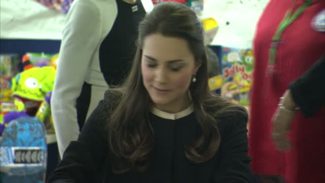 Interior shots of Catherine Duchess of Cambridge wrapping Christmas gifts during a visit to the Northside Centre in Harlem Catherine rolls her eyes...