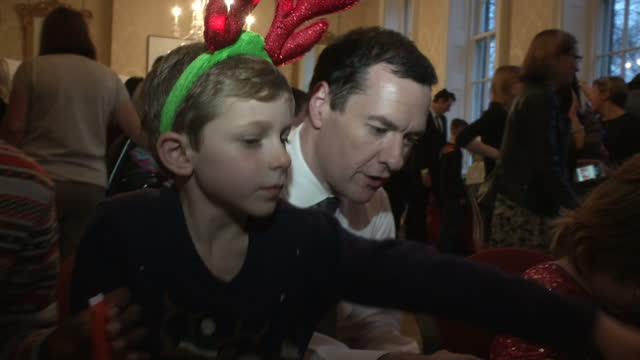 interior shots of chancellor george osborne sat with some of the children at the annual downing street christmas party making tree decorations on... - chancellor stock videos and b-roll footage