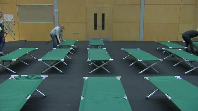 interior shots of charity workers collecting bedding from a pile and laying out rows of camp beds in a sports hall serving as a crisis at christmas... - homeless shelter stock videos & royalty-free footage