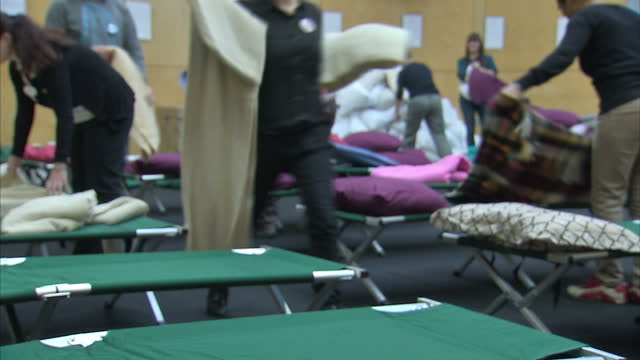 interior shots of charity workers collecting pillows and blankets and making up camp beds at a crisis at christmas homeless shelter. crisis charity... - homeless shelter stock videos & royalty-free footage