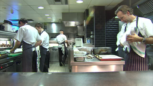 vídeos de stock e filmes b-roll de interior shots of chef patron marcus wareing and junior chefs at work in the kitchen of the marcus wareing restaurant at the berkeley. marcus wareing... - cozinha industrial