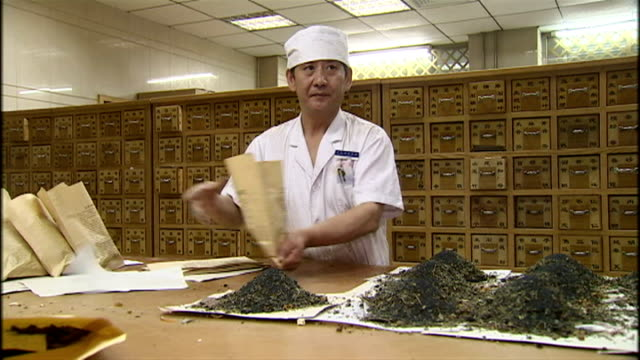 interior shots of chinese herbal medicine practitioners at work preparing piles of traditional herbal medicines on july 23 2009 in beijing china - kräuter stock-videos und b-roll-filmmaterial