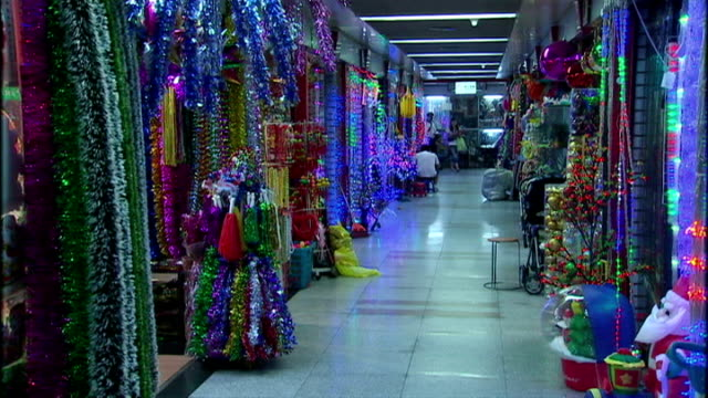 interior shots of christmas decorations on sale in a large wholesale market including tinsel strings of fairy lights and artificial christmas trees... - tinsel stock videos & royalty-free footage