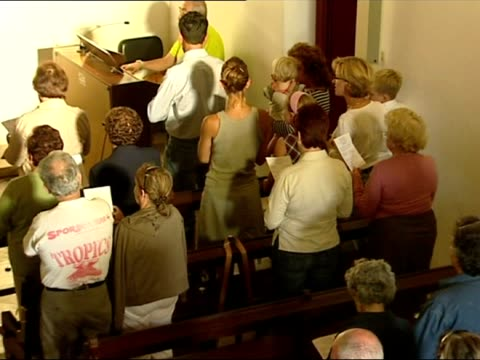 interior shots of church service mass taking place in memory of missing madeleine mccann with priest holding poster up during service church service... - poster stock videos & royalty-free footage