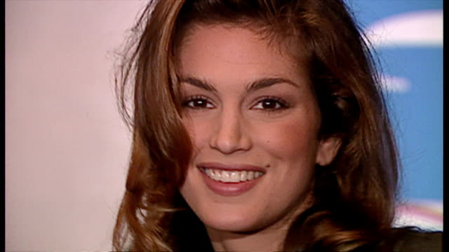 "interior shots of cindy crawford posing for photographs holding a copy of her new exercise video during a launch event for the ""cindy crawford: shape... - cindy crawford stock videos & royalty-free footage"