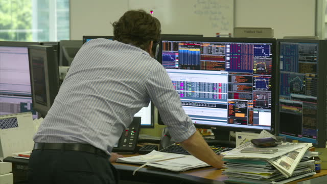 Interior shots of city traders in the Hong Kong Fidelity trading room looking at share prices on computer screens as a TV shows Sky News output of...