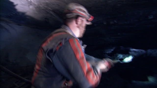 interior shots of coal miners working in a kentucky mine shoveling coal with coal moving along a conveyor belt on 20 april 2017 in hazard kentucky - ケンタッキー州点の映像素材/bロール