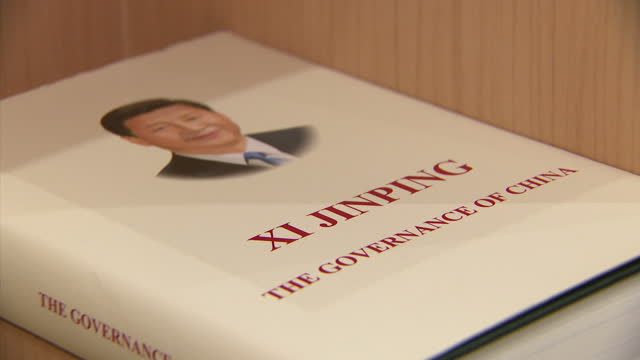 interior shots of copies of xi jinping's book 'the governance of china' with copies in english russian and mandarin on display at an exhibition... - ausstellung stock-videos und b-roll-filmmaterial