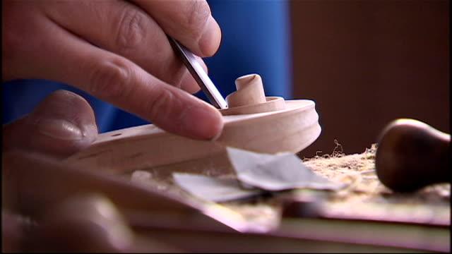vídeos y material grabado en eventos de stock de interior shots of craftsmen working on making new violins in a violin factory on december 21 2009 in beijing china - instrumento de cuerdas