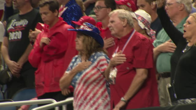 vidéos et rushes de interior shots of crowds of donald trump supporters sat for the star spangled banner national anthem before the president's campaign launch on 18... - célébrité