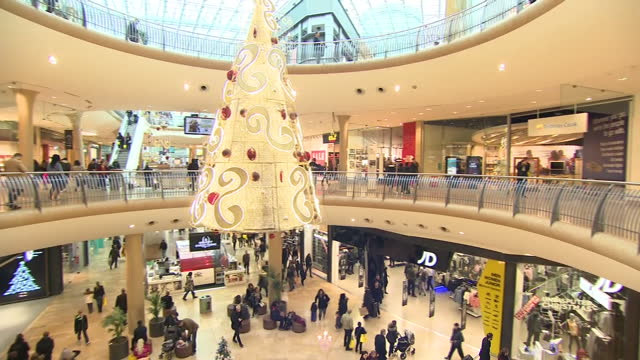 Interior shots of crowds of people walking through the Bullring shopping mall on Christmas Eve including shots of Christmas decorations around the...