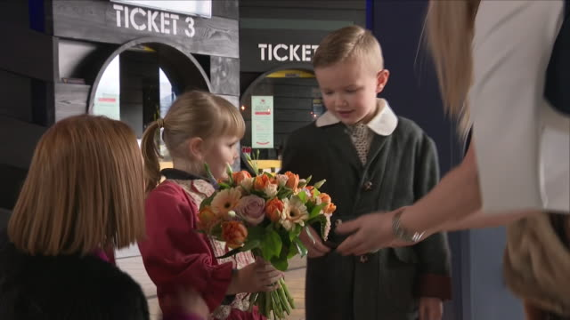 interior shots of crowds waiting for prince harry and meghan markle to arrive at the titanic museum and being greeted by children who present them... - titanic belfast stock videos & royalty-free footage