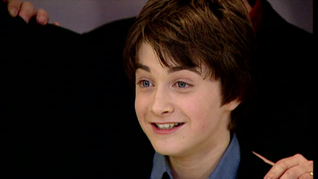 stockvideo's en b-roll-footage met interior shots of daniel radcliffe posing for photo op at the premiere of harry potter and the philosopher's stone on november 4 2001 in london... - harry potter naam kunstwerk