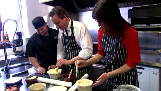 vídeos de stock, filmes e b-roll de interior shots of david cameron and samantha cameron making a pie in the kitchen of brains brewery. on april 07, 2015 in cardiff, wales. - pie humano