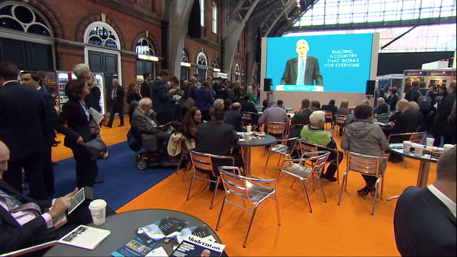 vídeos de stock e filmes b-roll de interior shots of delegates browsing the trade stands at the conservative party conference and watching chancellor philip hammond's speech via a big... - conferência partidária