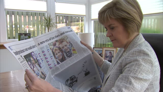 vídeos de stock e filmes b-roll de interior shots of deputy first minister nicola sturgeon reading the sunday times newspaper at a dining table, and reading articles on the scottish... - 2014