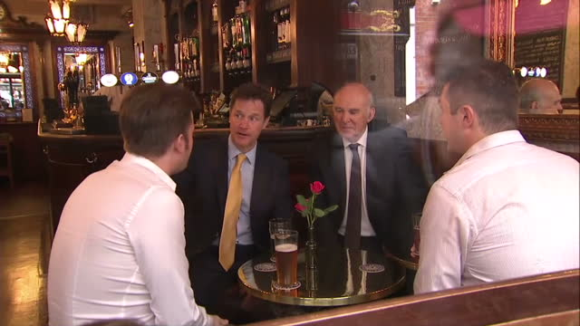 interior shots of deputy prime minister nick clegg business secretary vince cable sit together at a pub table laugh and chat drink a pint together on... - british liberal democratic party stock videos and b-roll footage