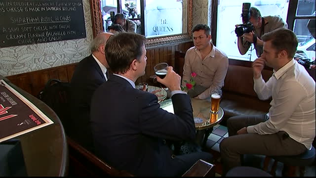 interior shots of deputy prime minister nick clegg business secretary vince cable meeting pub owners pull pints of bitter behind the bar sit together... - british liberal democratic party stock videos and b-roll footage