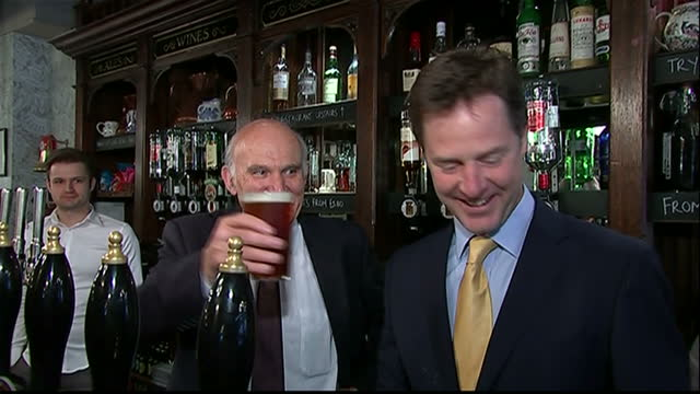 interior shots of deputy prime minister nick clegg pulling a pint of bitter for business secretary vince cable behind the bar at the queens head on... - ニック クレッグ点の映像素材/bロール