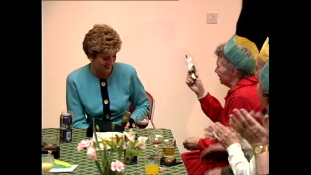 interior shots of diana princess of wales attending a party for elderly people at st matthew's community centre and pull a christmas cracker with a... - attending stock videos & royalty-free footage