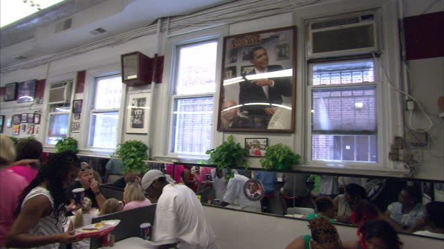 interior shots of diners in ben's chili bowl diner with a large framed picture of barack obama eating there on the wall on july 14, 2013 in... - us president stock videos & royalty-free footage