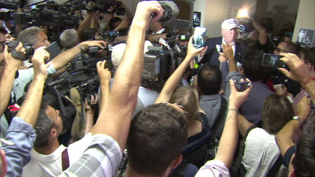 interior shots of donald trump surrounded by a press scrum speaking critically of fellow republican presidential candidate rick perry and saying that... - スクラム点の映像素材/bロール